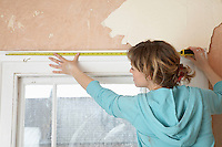 Woman  measuring  interior window frame back view