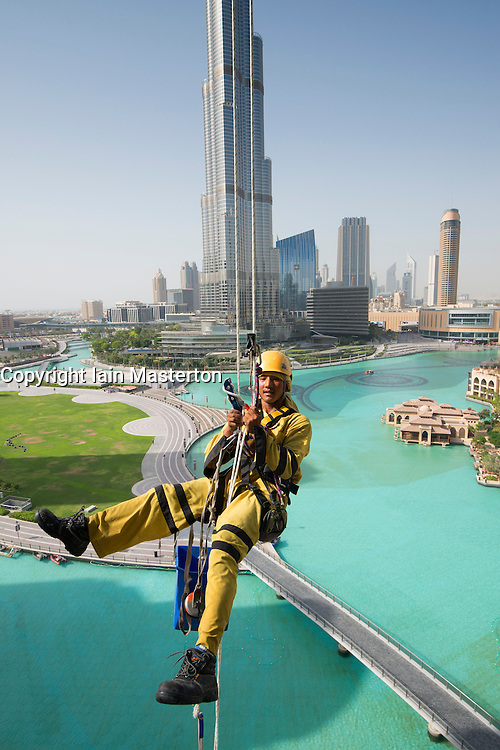 Window cleaners abseiling down high-rise apartment building in Dubai United Arab Emirates