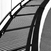 The metal railing of a bridge railing casts a shadow.
