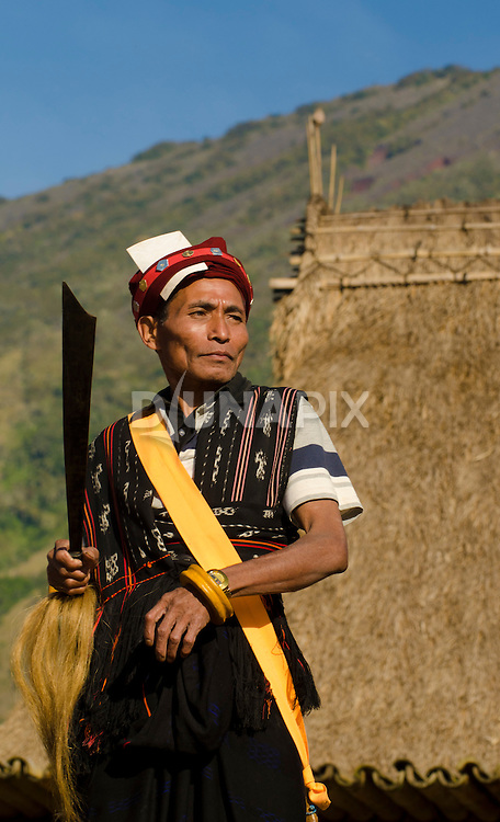 Man in traditional ceremeonial dress, carrying a parang knife, Luba Village, near Bajawa, Flores, East Nusa Tenggara, Indonesia