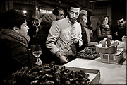 Young man making his choice of excellent mussels at the open air snack bar in Palermo. Lots of fresh local merchandise, except for the Dutch Creuse oysters in front of him, perfectly cooked and to be accompanied by a good wine. Palermo, Sicily, Italy