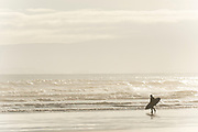 A silhouetted surfer heads into the waves at Oreti Beach, in Invercargill, New Zealand.