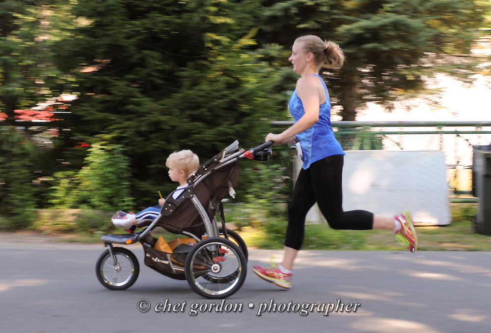 A runner pushes a baby carriage as she heads toward the finish line during the Greenwood Lake Inaugural 5K Run in Greenwood Lake, NY on Saturday, August 9, 2014.  © Chet Gordon/THE IMAGE WORKS