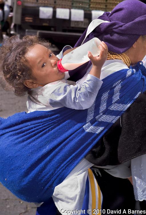Baby with bottle on mothers back, Otavalo, Imbabura, Ecuador