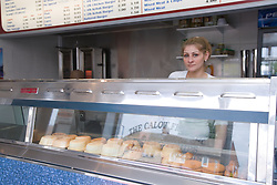 Bulgarian woman owner of Fish and chip shop standing behind counter,