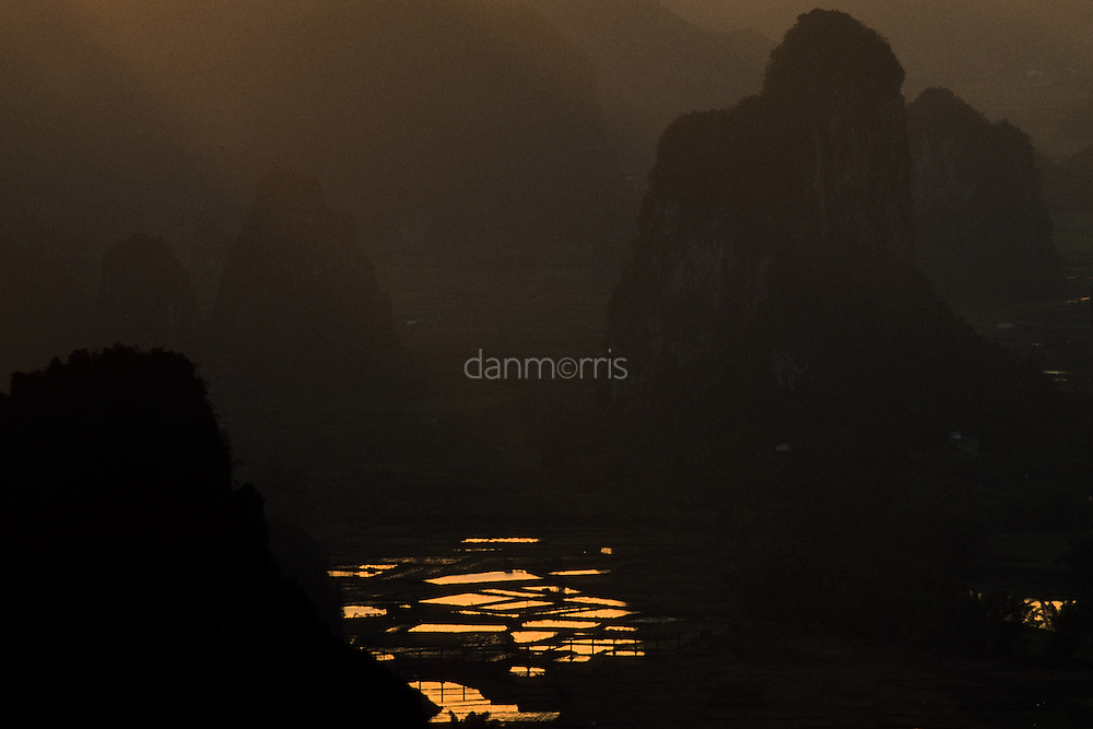Early morning light over landscape of rice paddies and myriad silhouetted karst towers, Yangshuo, Guilin, China