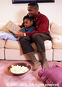 African-American father and daughter reading in living room (MR) Family, People,
