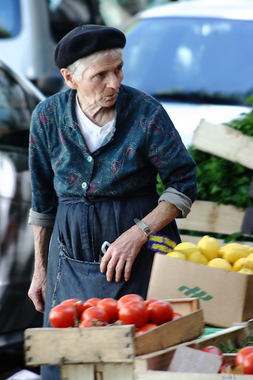 An old woman sells tomatoes and lemons in the market area of Croix-Rousse in Lyon, France