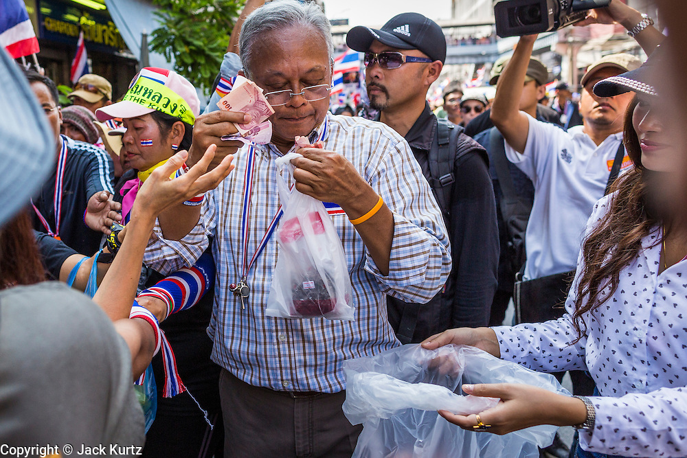 05 JANUARY 2014 - BANGKOK, THAILAND: SUTHEP THAUGSUBAND, leader of the anti-government movement, stuffs cash offered by supporters into a garbage bag during a march through Bangkok Sunday. People handed hundreds of thousands of Thai Baht to Suthep as he led the march. Suthep is a former Deputy Prime Minister and member of the opposition Democrat Party who resigned to organize the protests against the Pheu Thai government.  He led the protestors on a march through the Chinatown district of Bangkok. Tens of thousands of people waving Thai flags and blowing whistles gridlocked what was already one of the most congested parts of the city. The march was intended to be a warm up to their plan by protestors to completely shut down Bangkok starting Jan. 13.     PHOTO BY JACK KURTZ