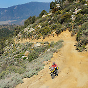 BMW F800GS motorcycle riding dirt road in Mohave desert canyon in California