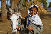 December 1992, Egypt --- A boy leads his donkey down a road in Egypt. --- Image by © Owen Franken/CORBIS