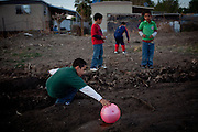 Seven-year-old Naftale Gutierrez reaches for a ball in mud contaminated by raw sewage from the Rancho Garcia trailer park and agricultural fertilizers in Thermal, Calif., March 8, 2012.