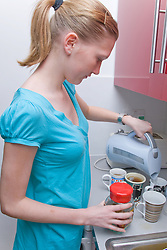 Teenaged girl on work experience placement from school making a round of coffee in the work place,