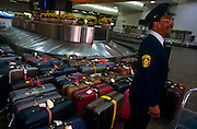 A security guard stands over unattended baggage at Atlanta Hartsfield airport's arrivals hall carousel.