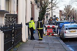 A police officer speaks with a firefighter at the cordoned off entrance to 29 Holland Park Gardens after a fire in a flat on the first floor of the converted house claims the life of a man and his dog in Holland Park, West London. February 07 2018.