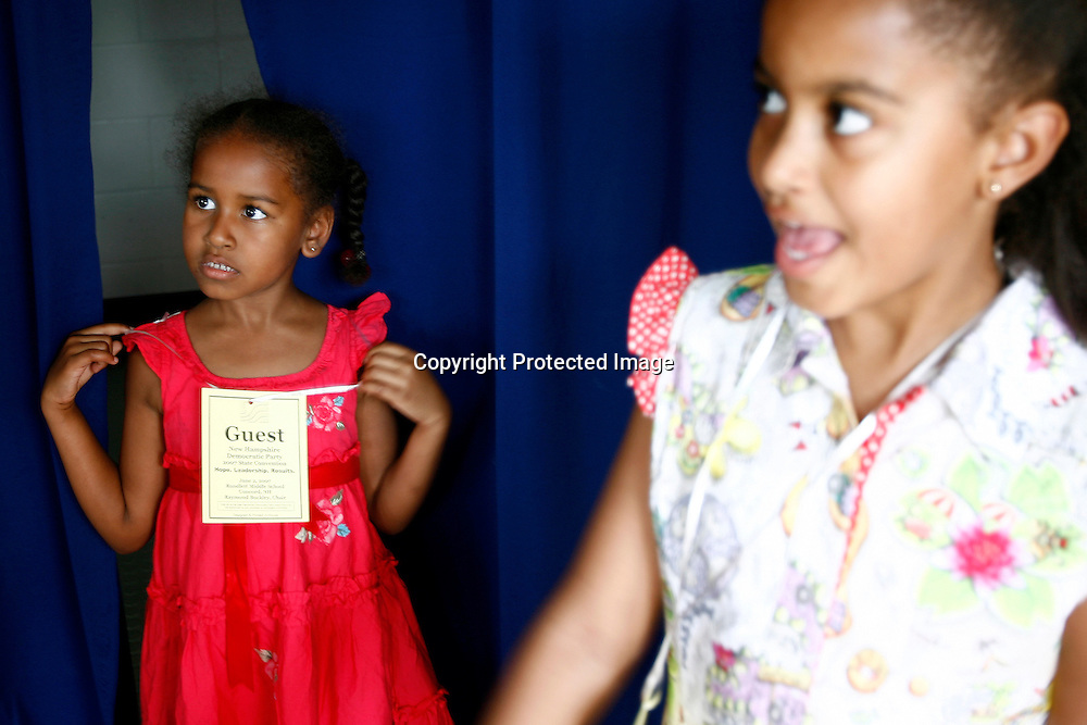 Sasha and Malia(R) Obama, daughters of Democratic presidential hopeful Senator Barack Obama, watch as their mother Michelle Obama speaks to supporters during a rally in Concord, New Hampshire June, 2, 2007. .