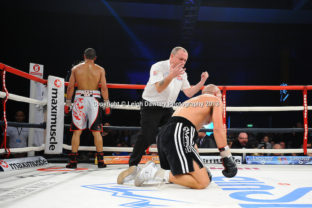 Chris Eubank Jnr knocks down Frankie Borg. Borg gets the count from the referee, whilst Eubank Jnr stands in the corner seeking acknowledgment from the crowd. A Middleweight contest. Glow, Bluewater, Kent, UK. Hennessy Sports © Leigh Dawney Photography 2013.