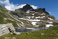 A female hiker is resting on a rock close to the lake Geisspfadsee, Landschaftspark Binntal, Valais, Switzerland