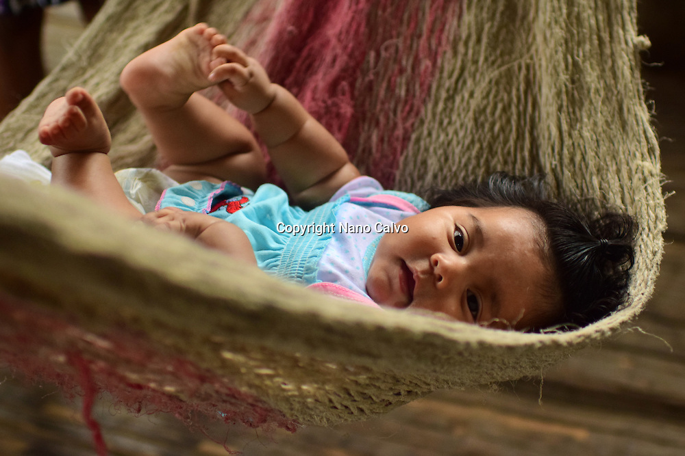 Female bribri baby (Simea) in handmade hammock inside a hut. <br />