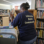 WASHINGTON, DC - SEP9: Denise Barnes, a library technician, shelves books for the opening of the new Woodridge Public Library, the latest library to reopen in D.C. with an innovative design, September 9, 2016. (Photo by Evelyn Hockstein/For The Washington Post)
