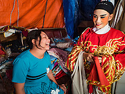 04 OCTOBER 2016 - BANGKOK, THAILAND: A nonperforming member of the Chinese opera troupe talks to a performer before the opera performance at the Vegetarian Festival at the Chit Sia Ma Chinese shrine in Bangkok. The Vegetarian Festival is celebrated throughout Thailand. It is the Thai version of the The Nine Emperor Gods Festival, a nine-day Taoist celebration beginning on the eve of 9th lunar month of the Chinese calendar. During a period of nine days, those who are participating in the festival dress all in white and abstain from eating meat, poultry, seafood, and dairy products. Vendors and proprietors of restaurants indicate that vegetarian food is for sale by putting a yellow flag out with Thai characters for meatless written on it in red.     PHOTO BY JACK KURTZ