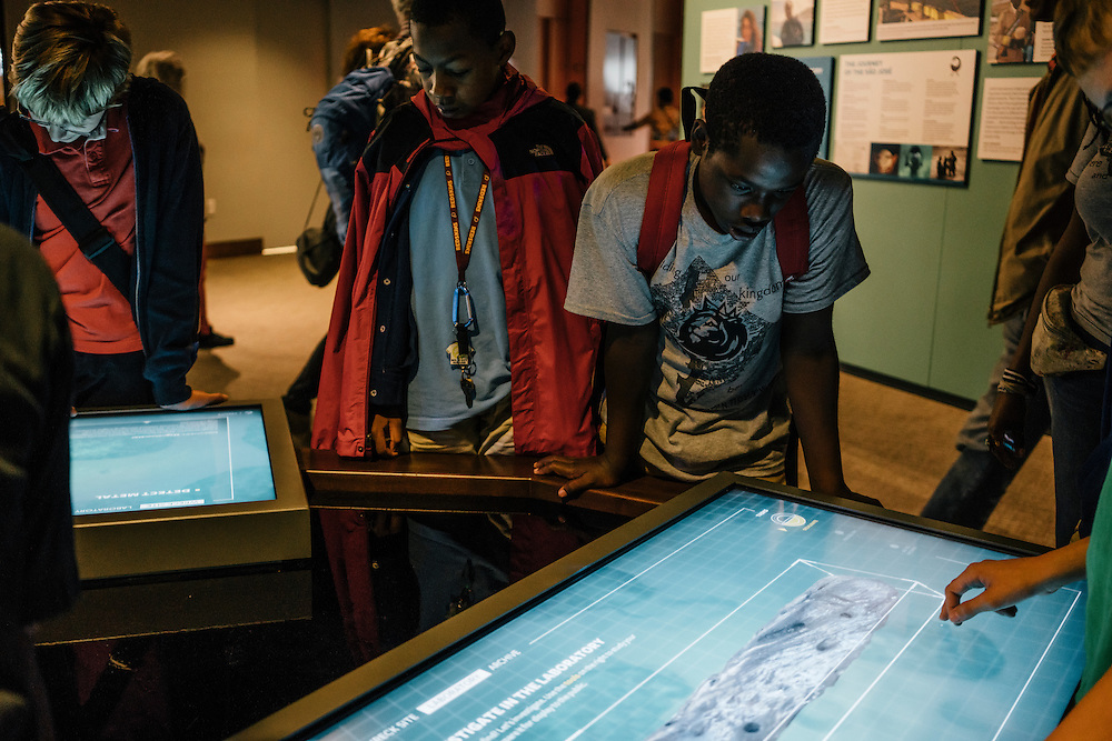 Sixth-graders from Knowledge Is Power Program (KIPP) DC, including Tay'sean Barrow, 12, center, looks at an interactive display inside the Smithsonian National Musuem of African American History and Culture during their visit on Oct 21, 2016. The students spent an hour touring the new Washington, D.C. museum, which is only available to see with reserved tickets during the first year.
