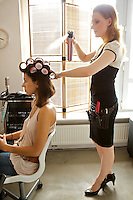 Female hairdresser spraying hairspray in customer's hair
