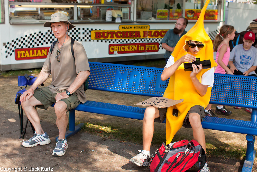 """01 SEPTEMBER 2011 - ST. PAUL, MN:  A high school student in a banana suit at the Minnesota State Fair. The teenager said he wore the suit to the fair to see how people would react to him. The Minnesota State Fair is one of the largest state fairs in the United States. It's called """"the Great Minnesota Get Together"""" and includes numerous agricultural exhibits, a vast midway with rides and games, horse shows and rodeos. Nearly two million people a year visit the fair, which is located in St. Paul.   PHOTO BY JACK KURTZ"""