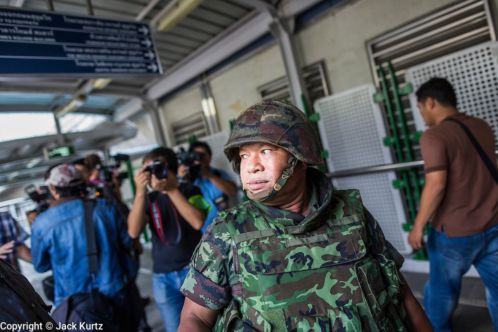 "01 JUNE 2014 - BANGKOK, THAILAND: A Thai soldier patrols the Asok BTS Skytrain station in Bangkok after a flash mob protested against the coup near the station. The Thai army seized power in a coup that unseated a democratically elected government on May 22. Since then there have been sporadic protests against the coup. The protests Sunday were the largest in several days and seemed to be spontaneous ""flash mobs"" that appeared at shopping centers in Bangkok and then broke up when soldiers arrived. Protest against the coup is illegal and the junta has threatened to arrest anyone who protests the coup. There was a massive security operation in Bangkok Sunday that shut down several shopping areas to prevent the protests but protestors went to malls that had no military presence.    PHOTO BY JACK KURTZ"