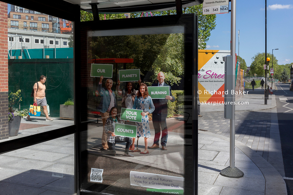 In the UK, 32,313 people have now died after testing positive for coronavirus which is now the highest death toll in Europe, even exceeding that of Italy. As the UK lockdown continues with social distancing measures still in effect, a local man carries shopping past a bus stop showing a Green New Deal poster promoting a series of policy proposals to tackle global warming and the current financial crisis, on 5th May 2020, in London, England.