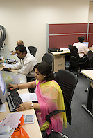 An Indian woman wears the traditional sari in the offices of Axiom telecom. Dubai, one of the seven emirates and the most populous of the United Arab Emirates sits on the southern coast of the Persian gulf.