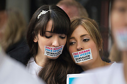 © London News Pictures. 02/11/2013.  London, UK. NANCY THORBURN (Left), girlfriend of imprisoned Greenpeace journalist  Kieron Bryan wearing a sticker over her mouth at a silent demonstration outside the Russian Embassy in London to protest against the arrest of Kieron Bryan and 30 Greenpeace activists, known as the 'Arctic 30' , following a peaceful protest against Arctic oil drilling at an oil platform in the Pechora Sea. Photo credit Ben Cawthra/LNP