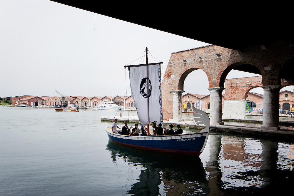 VENICE, ITALY - 29 MAY 2013: Ragnar Kjartansson's &quot;&quot;SS Hangover&quot; (2013) - Boat, captain, brass instruments, musicians and music by Kyarta Sveinsson - navigates in the Gaggiandre, a docking in the XVI century shipyards of the Arsenale, in Venice, Italy, on May 29th 20113. <br /> <br /> Ragnar Kjartansson has turned an old, wooden Icelandic fishing boat into the S.S. Hangover, a vessel he named after a boat-shaped bar featured in the 1935 mystery comedy film &quot;Remember Last Night?&quot;. In the Gaggiandre, a docking area in the XVI century shipyards of the Arsenale, Kjartansson stages a performance featuring a crew of professional musicians who play while ferrying the boat back and forth from one dock to the next in a procession that alludes to the XVI Venetian tradition of Theatres of the World.<br /> <br /> The 55th International Art Exhibition of the Venice Biennale takes place in Venice from June 1st to November 24th, 2013 at the Giardini and at the Arsenale as well as in various venues the city. <br /> <br /> Gianni Cipriano for The New York TImes