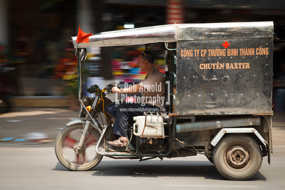 © Rob Arnold.  19/04/2013. Hanoi, Vietnam. A man driving an ambulance on the streets of Hanoi, Vietnam. Photo credit : Rob Arnold