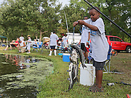 JD Vanc, 8, of Cedar Rapids, pulls in his stringer of fish during the 10th annual Boys & Girls Clubs of Cedar Rapids Fish-O-Rama at Robbins Lake in Cedar Rapids on Saturday, August 4, 2012. Organizers expected 1,200-1,500 participants in the weekend event. There were 426 prizes available to people who caught tagged fish. Prizes included a Toyota truck, boat, TVs, grills, bicycles, and gift certificates.