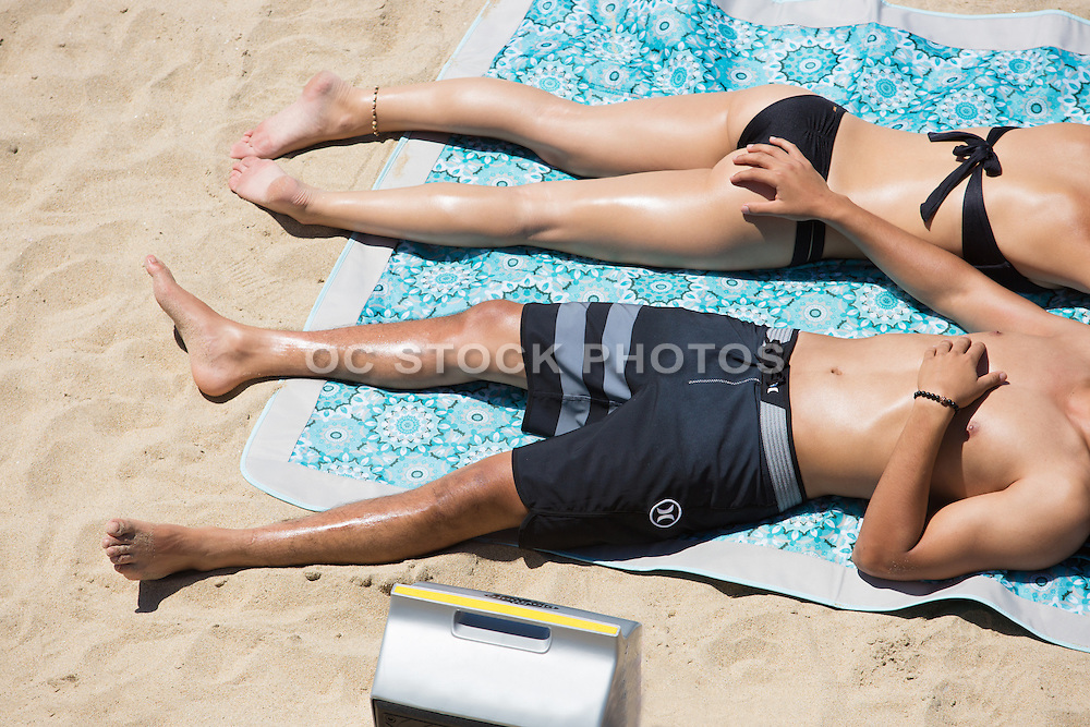 Young Couple Sunbathing on the Beach at Huntington Beach Pier