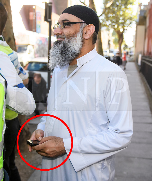© Licensed to London News Pictures. 19/10/2018. London, UK. Radical preacher ANJEM CHOUDARY is seen using a mobile phone (circled red) before posing for media outside a bail hostel after being released form Belmarsh Prison in south-east London. Choudary was jailed in 2016 for inviting support for for Islamic State of Iraq and the Levant (ISIS). Photo credit: Ben Cawthra/LNP