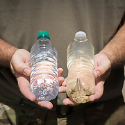 OCTOBER 25 - UTUADO, PUERTO RICO - <br /> Sgt. Gary Wyckoff holds two containers with water, one unfiltered and another filtered at a station next to the Lago Dos Bocas in Utuado. Troops from Fort Bragg, NC, are using a water filtration system to purify the liquid.<br /> (Photo by Angel Valentin/Freelance)