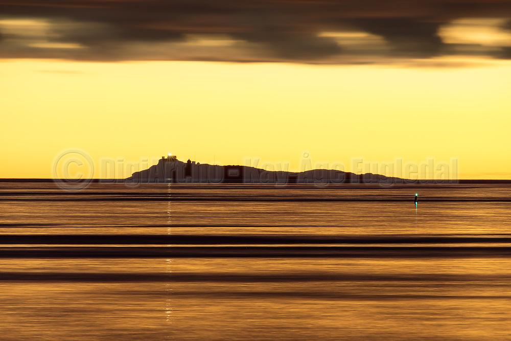 The island Svinøya, on the west coast of Norway, surrounded by golden sea during amazing sunset. Captured with 600mm and long shutter speed | Svinøya omgitt av gyllen sjø. Tatt med 600mm brennvidde, og lang lukketid under en fantastisk solnedgang.
