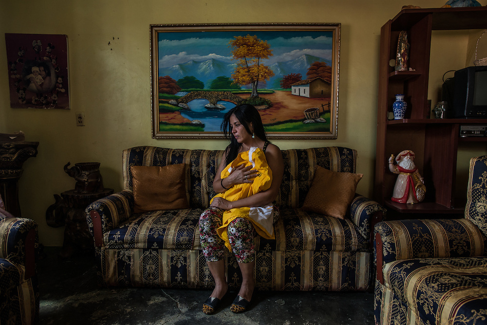"LA VELA, VENEZUELA - SEPTEMBER 10, 2016: Saribeth Cordero poses for a portrait in her living room holding her missing brother's barbershop uniform.  Her brother, William Cordero, disappeared after leaving with a smuggler and other migrants to travel illegally by boat and look for work in Curaçao. The plan had been a simple one: A seven-hour journey in a speedboat. If they were stopped by Curaçao's coast guard, they would pose as tourists. And with their documents in plastic bags, they were ready to swim ashore, knowing that the smuggler wanted to make a quick getaway. Then they could find their contacts using cell phones tucked in empty rice porridge jars. The migrants waited anxiously in La Vela for several days as the smuggler got reports from other fishermen in Curaçao about coast guard patrols, trying to decide which night would be safest to leave. Saribeth, recalled the group sitting in her brother's barber shop on her porch one afternoon as a movie played on the television about a shipwreck.""What if there are sharks?"" asked one of the migrants, Ms. Cordero recalled. ""You can't be negative like that,"" Mr. Cordero said, his sister recalled. But she said her brother was scared too. ""He was nervous about the ocean,"" Ms. Cordero said. PHOTO: Meridith Kohut for The New York Times"