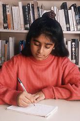 Portrait of teenage girl sitting at desk writing letter,