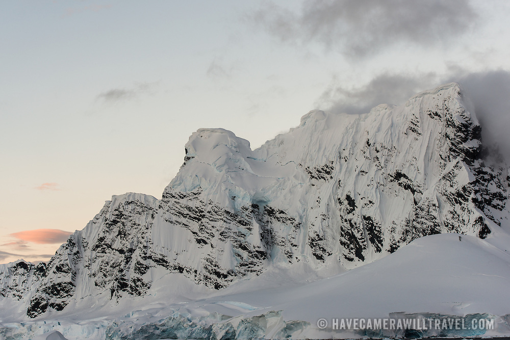 Steep mountain cliffs of rock and ice rise above Paradise Harbor, Antarctica, as the sun sets.