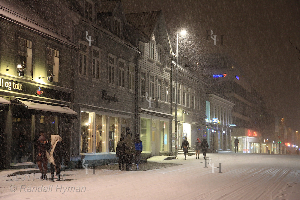 January snowstorm pelts midnight revelers bundled in winter coats and stylish clothes in downtown Tromso, Norway.