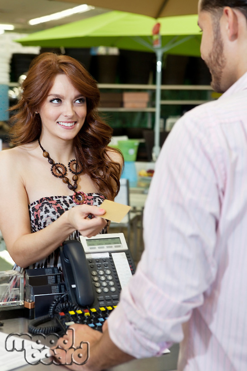 Beautiful young woman paying through credit card in store