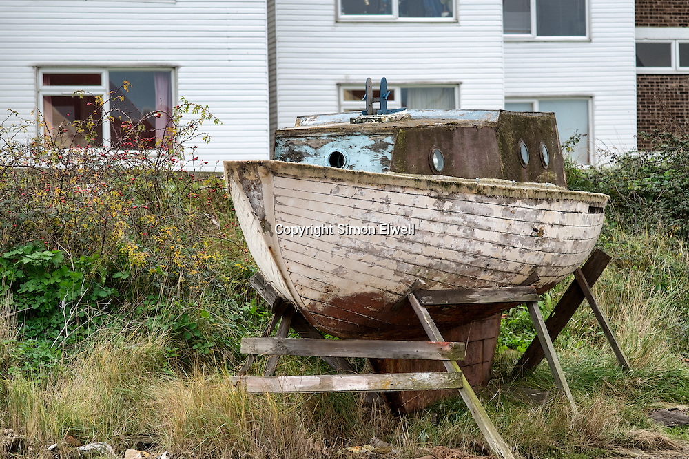A once-loved boat sits disused in a boat yard showing signs of the weather