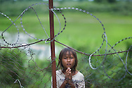 A little girl begs for money outside the barbed wire fence at the Killing Fields museum in Cambodia. The museum was a former school in Phnom Pehn used as a prison where Cambodians were interrogated, tortured, and murdered by the Khmer Rouge. The Khmer Rouge ruled Cambodia from 1975 to 1979.  While in power the Khmer Rouge murdered, worked to death, or killed by starvation close to 1.7 million Cambodians, or more than one-fifth of the country?s population..