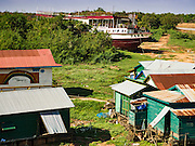 31 MAY 2016 - SIEM REAP, CAMBODIA: The Tara beached just beyond a village a few miles from the Tonle Sap Lake. The Tara is a river freighter and passenger boat assembled in Vietnam, then a French colony, in 1927. Most recently it's used to take tourists on dinner cruises on the Tonle Sap Lake. Because of the drought in Cambodia, the Tara is beached and unable to navigate the nearly empty canals that lead to the Tonle Sap Lake. The boat's owners are repairing and refurbishing it while it's beached and hope that the coming rainy season will flood the canal enough to let the Tara get back to the lake.    PHOTO BY JACK KURTZ