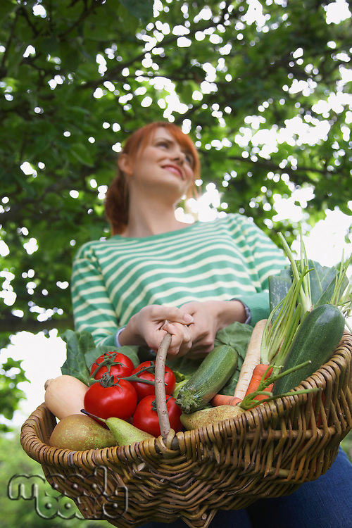 Woman holding fruit and vegetable basket outdoors