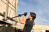 Mid-adult man adjusting strapping of truck loaded with wood