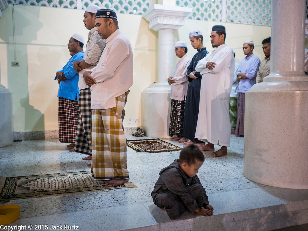18 JUNE 2015 - PATTANI, PATTANI, THAILAND:  Men pray during Ramadan services at Pattani Central Mosque. Thousands of people come to Pattani Central Mosque in Pattani, Thailand, to mark the first night of Ramadan. Ramadan is the ninth month of the Islamic calendar, and is observed by Muslims worldwide as a month of fasting to commemorate the first revelation of the Quran to Muhammad according to Islamic belief. This annual observance is regarded as one of the Five Pillars of Islam. Islam is the second largest religion in Thailand. Pattani, along with Narathiwat and Yala provinces, all on the Malaysian border, have a Muslim majority.    PHOTO BY JACK KURTZ